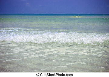 Sea waves in azure water at the blue sky bakcground