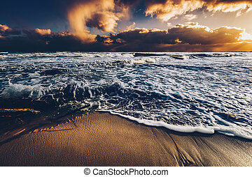 Sea waves on a sandy shore at sunset.