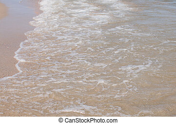 sea waves on a sandy shore in the afternoon
