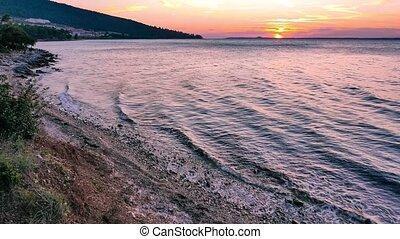 Sea waves on sandy beach at sunset. 4k