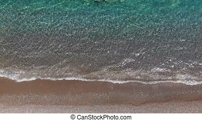sea waves roll on brown beach reflecting bright sunlight -...