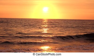 Sea waves rolled on a sandy beach in the rays of the setting...