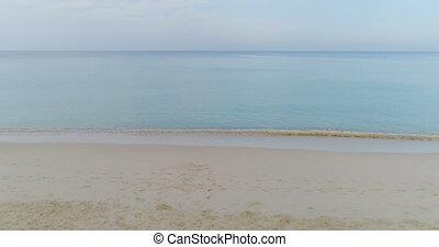 Sea waves rolling on empty sandy beach
