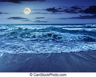sea ??waves running on sandy beach at night - green and...