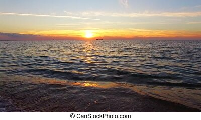 Sea Waves Splashing Against The Shore At Sunset