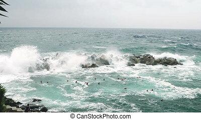 Sea waves splashing through a gap in the rocks.