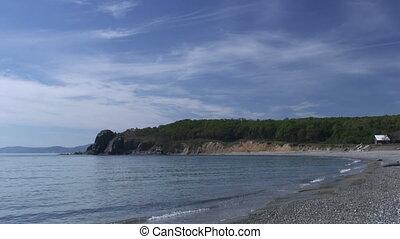 Sea waves surf on stony rocks beach. Japan Sea.