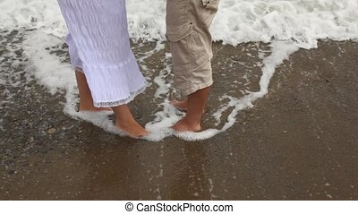 Sea waves wash feet of woman and men