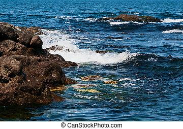 Sea waves wash large rocks