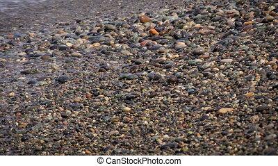 sea waves washes pebble beach, closeup