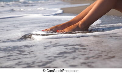 Sea waves washing over tanned female feet. Beautiful young...
