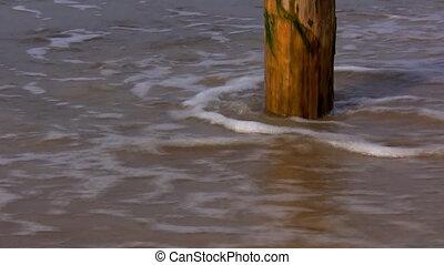 Sea waves washing pole on the beach