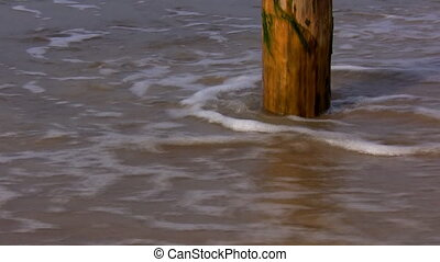 Sea waves washing pole on the beach