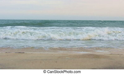 Sea waves washing sandy beach