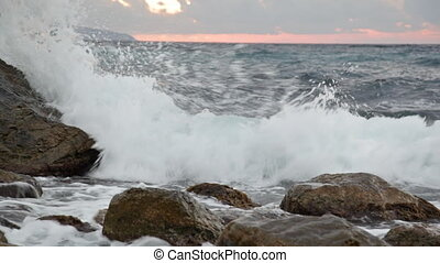 Sea waves with splashes break about stones early in the morning at sunrise