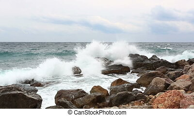 Sea waves with splashes break about stones early in the morning
