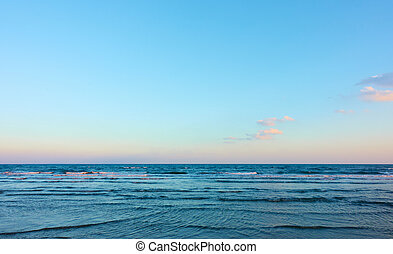 Sea with clear horizon and blue sky with clouds - background