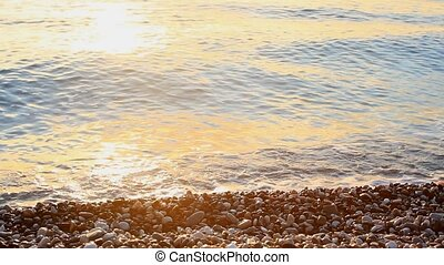 Sea with pebbles splashing at sunrise in Antaly