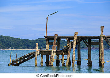 Sea with pier under blue cloudy sky