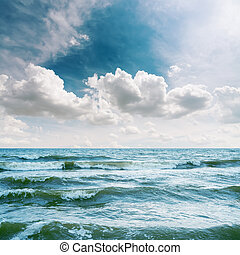 sea with waves and dramatic sky over it
