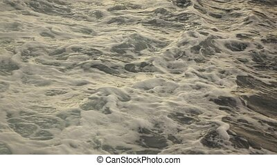 sea with waves and foam - sea wave foaming behind a boat...
