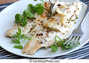 Seabass fillets with watercress on a plate