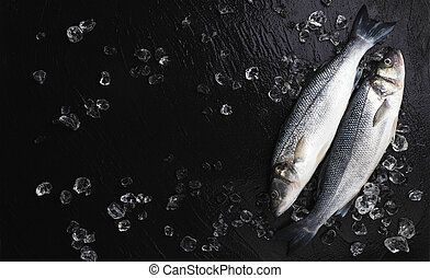 Seabass fish on ice on black stone background, top view