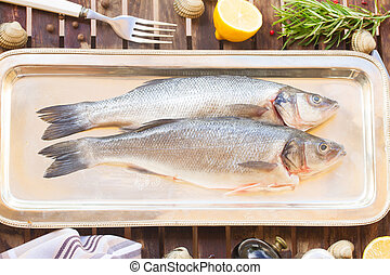 Seabass - Two fresh raw  seabass  fish on silver tray