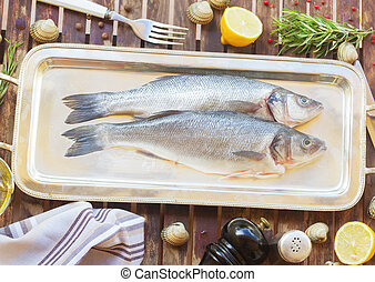 Seabass - Two fresh raw seabass fish on silver tray with...