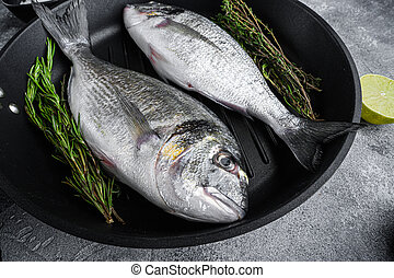 Seabream or dorado raw fish on grill pan with ingredients on grey white textured background, side view selective focus.