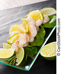 Seafood ceviche from hake on a glass plate with lime and greens