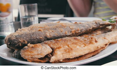 Seafood Cooked Fried Fish Trout on a Plate in a Restaurant -...