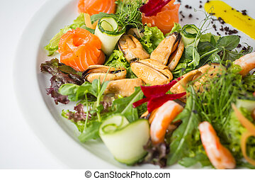 Seafood fresh salad with shrimps, mussels, salmon, green and cucumber