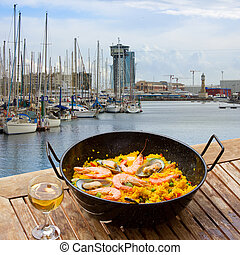 Seafood paella with glass of wine in seaside cafe, port of Barcelona