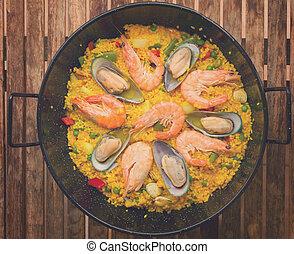 Seafood Paella in black pan -traditional spanish rice dish, retro toned