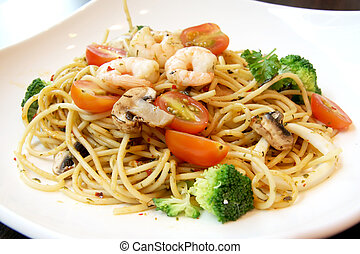 Seafood pasta with prawns and mushrooms on white plate