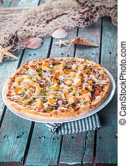 Seafood Pizza on Rustic Wood Table with Shells - Close Up of...