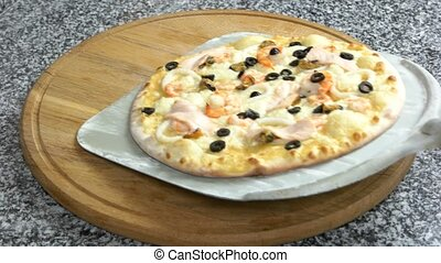 Seafood pizza on wooden board.