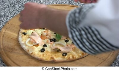 Seafood pizza with basil leaves. Baked food close up.