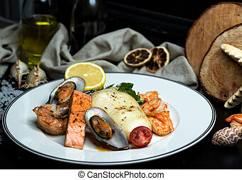 seafood plate with fried salmon, mussels, shrimps, calamari and lemon