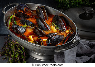 Seafood soup with mussels and crabs in metal pot