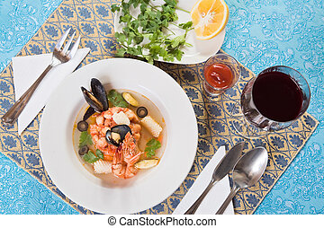 Seafood soup with shrimps and mussels on blue ornate table-cloth