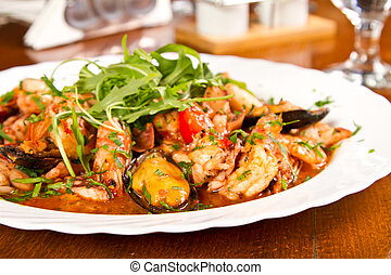 Seafood stew with rucola salad