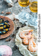 Seafood with two glasses of white wine on the wooden table