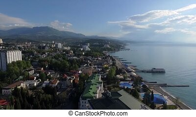 Seafront of Alushta in Crimea from drone in spring with piers cuts Black sea