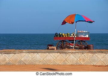 seafront view of vendor's cart with fruits