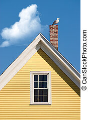 Seagull resting on chimney on house with yellow gable against blue sky with clouds
