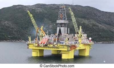 Seagulls fly over drilling platform in gulf of Stavanger