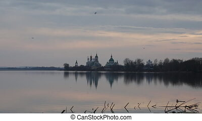 Seagulls fly over Nero's lake against Spaso-Yakovlevsky Monastery in Rostov on a sunset in the early spring