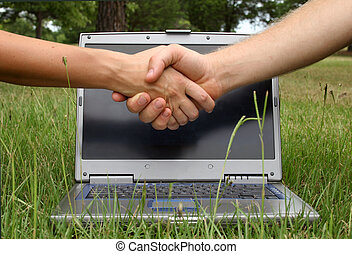 Business handshake; laptop background